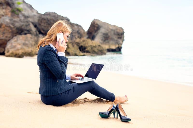 Geschäftsfrau, die an dem Strand mit Laptop-Computer arbeitet lizenzfreie stockfotografie
