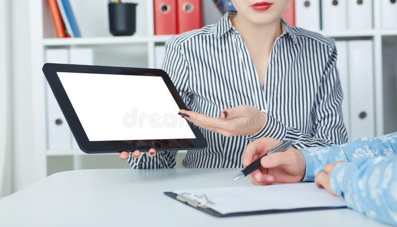 Geschäftsfrau, die den Mitarbeitern digitale Tablette im Büro zeigt stockbild
