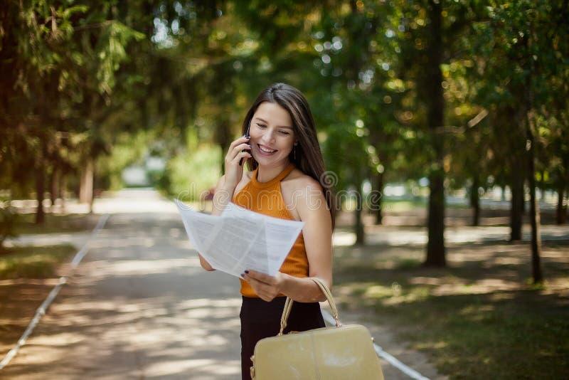 Geschäftsfrau, die in den Park in der Hand spricht am Telefon mit Dokumenten geht Gl?ck und Gel?chter Gute Nachrichten stockfoto