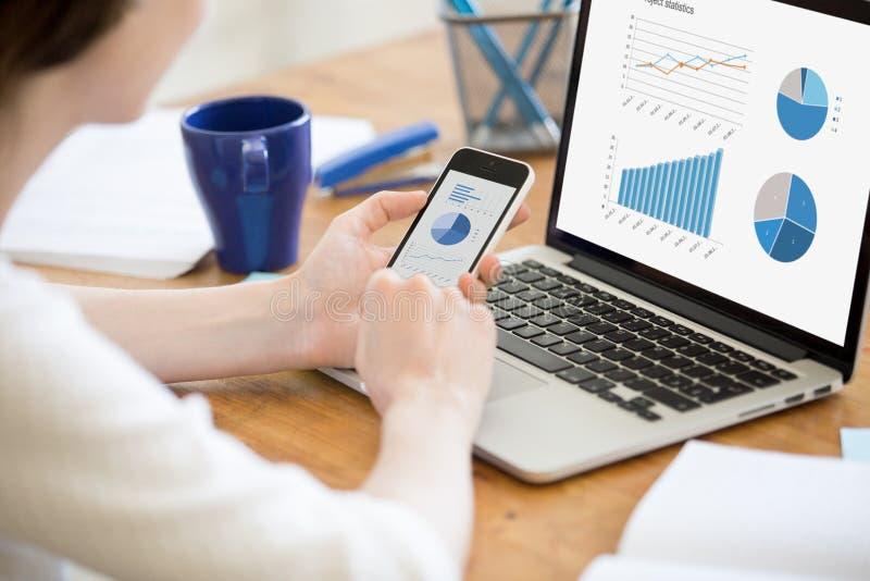 Geschäftsfrau, die den Smartphone, arbeitend mit Laptop, unter Verwendung der Kundenberaterin hält stockfotografie