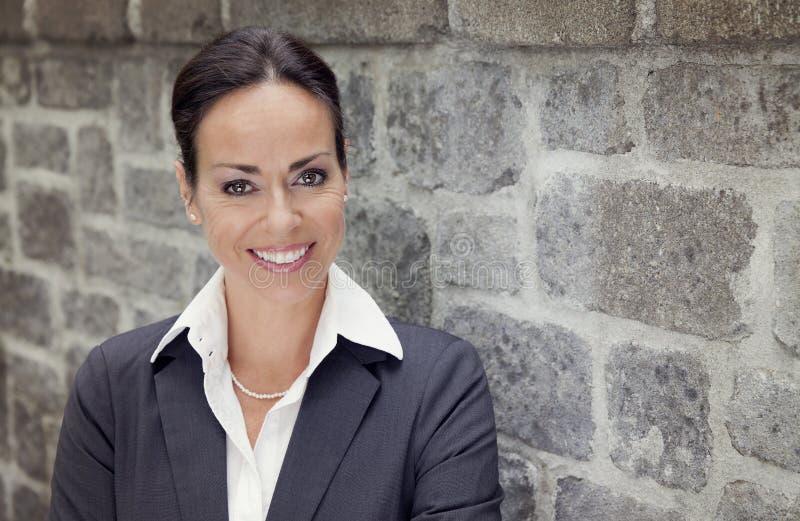 Geschäftsfrau, die an der Kamera lächelt lizenzfreie stockfotografie