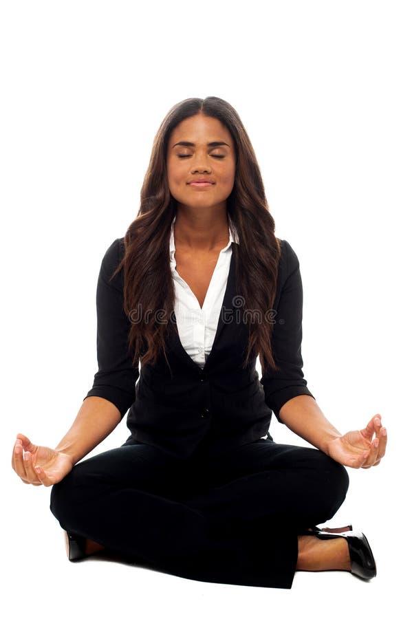 Geschäftsfrau, die in der Lotoslage meditiert stockbilder