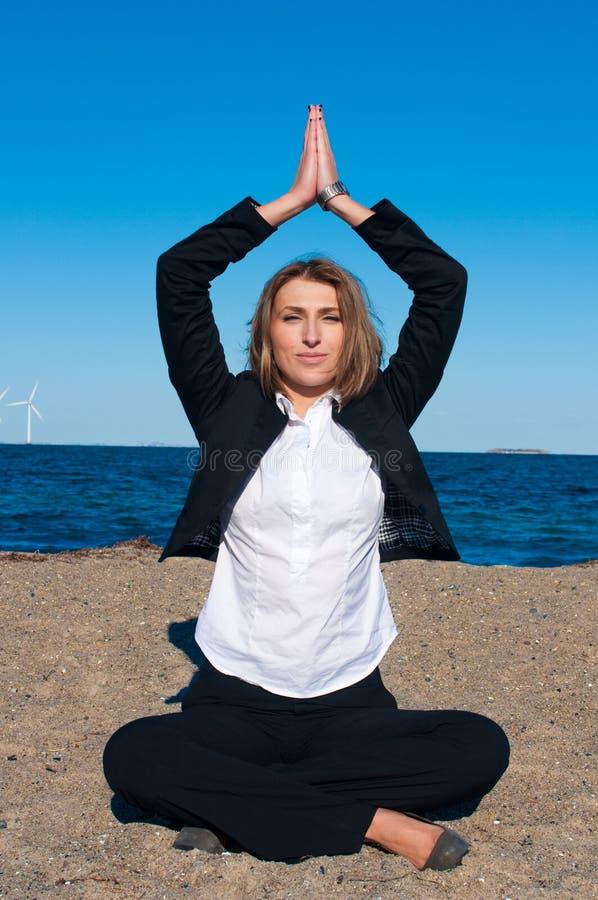 Geschäftsfrau, die in der Yogahaltung auf dem Strand sitzt stockbild