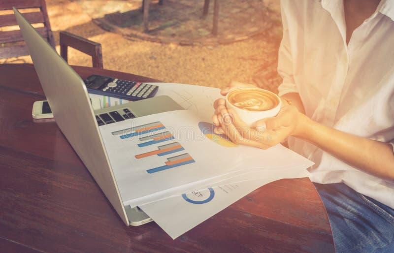 Geschäftsfrau, die Diagrammdokument mit Laptop analysiert und Kaffeeweinleseton hält lizenzfreies stockfoto