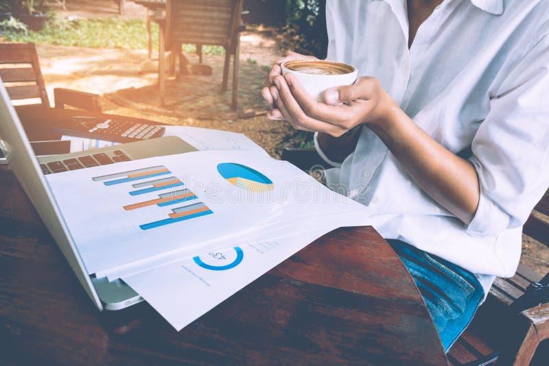 Geschäftsfrau, die Diagrammdokument mit Laptop analysiert und Kaffeeweinleseton hält stockfoto