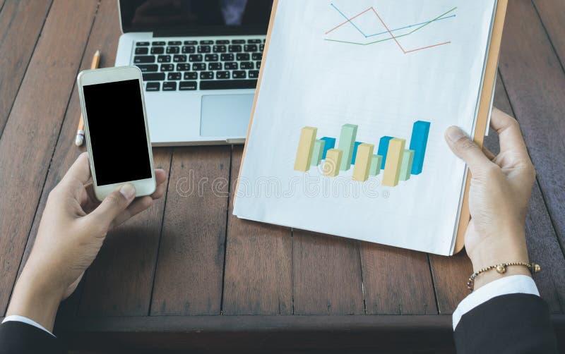 Geschäftsfrau, die Diagrammdokument mit Laptop und Gebrauchshandy analysiert stockfoto