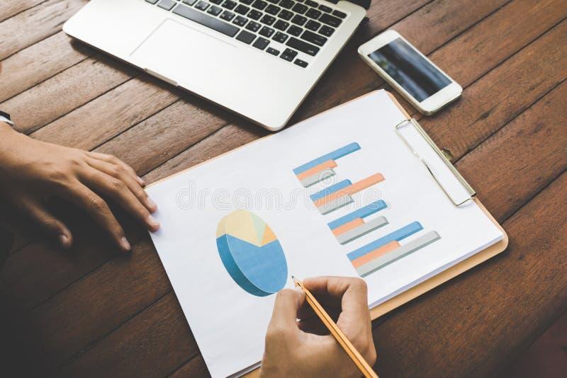 Geschäftsfrau, die Diagrammdokument mit Laptop- und Handydunkelheitston analysiert lizenzfreies stockfoto