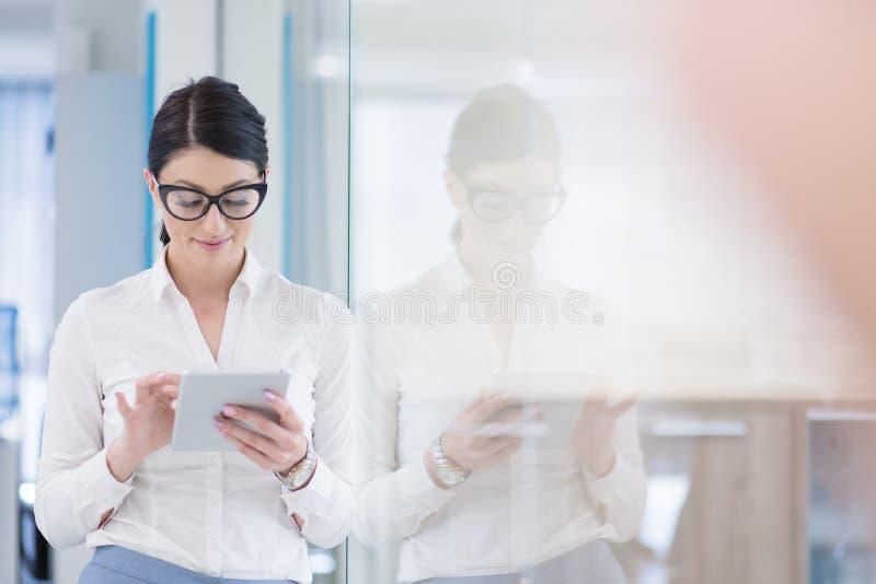 Geschäftsfrau, die Digital-Tablet vor Startbüro verwendet stockfoto