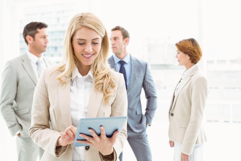 Geschäftsfrau, die digitale Tablette mit Kollegen hinten verwendet lizenzfreies stockbild
