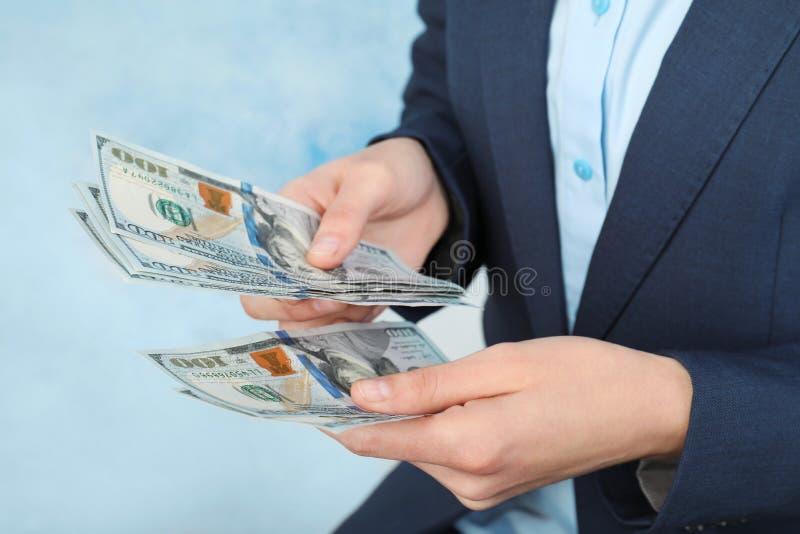 Geschäftsfrau, die Dollar auf Farbhintergrund zählt lizenzfreies stockbild