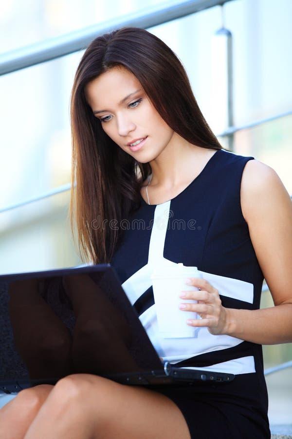 Geschäftsfrau, die draußen Laptop auf Schritten verwendet lizenzfreie stockbilder