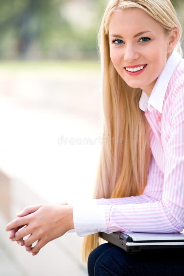 Geschäftsfrau, die draußen sitzt stockfoto