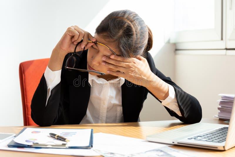 Geschäftsfrau, die durch das Schließen des Auges beim Arbeiten im Büro stillsteht stockbild