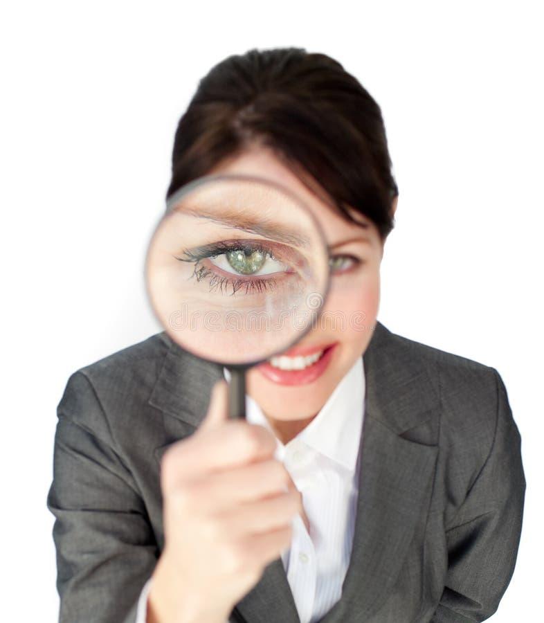 Geschäftsfrau, die durch ein Vergrößerungsglas schaut lizenzfreies stockfoto