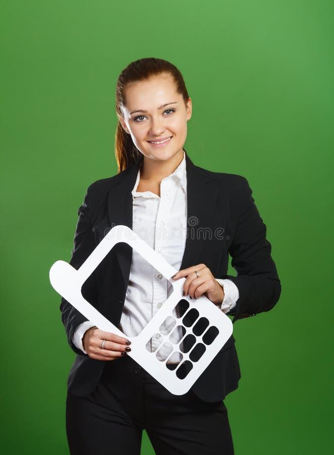 Geschäftsfrau, die durch Papierhandy auf grünem backg schaut lizenzfreie stockfotografie