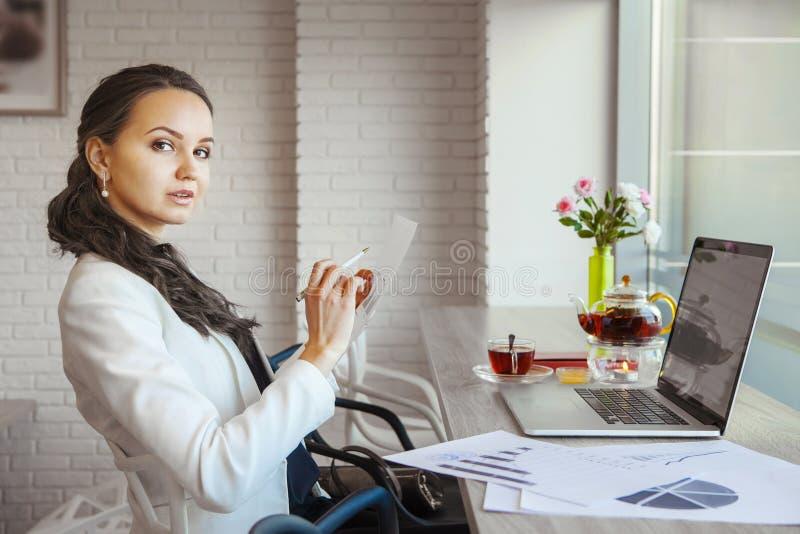 Geschäftsfrau, die durchdacht Rahmenbehälter und -papier mit Diagrammen untersucht lizenzfreie stockfotos