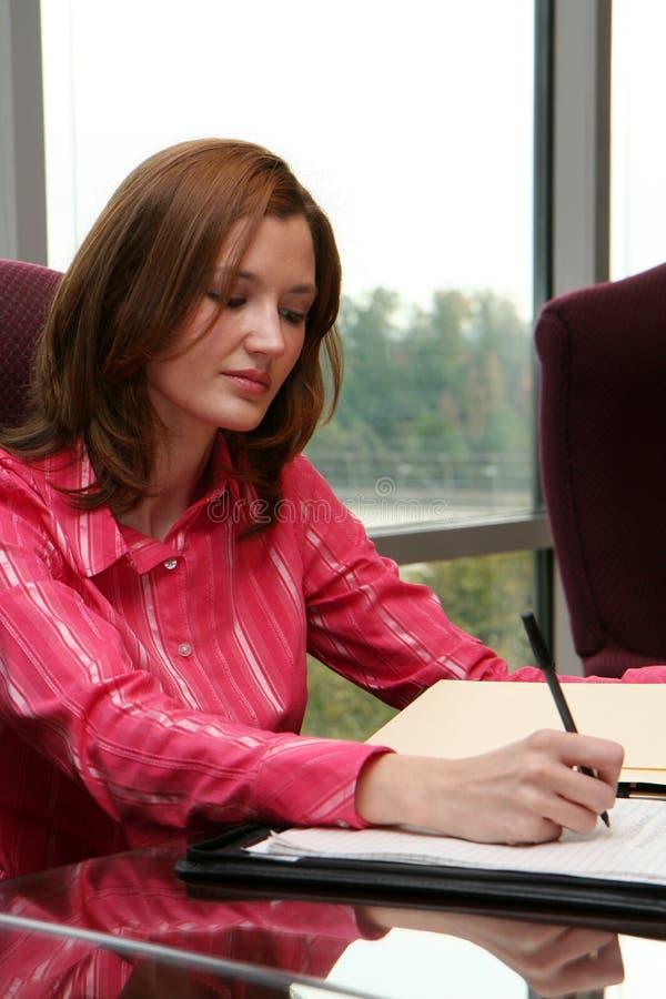Geschäftsfrau, die ein Angebot schreibt stockfotografie