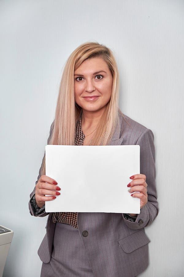 Geschäftsfrau, die ein Blatt Papier hält und Kamera betrachtet lizenzfreies stockbild