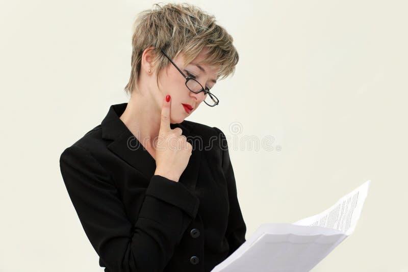 Geschäftsfrau, die ein Papier liest lizenzfreie stockbilder