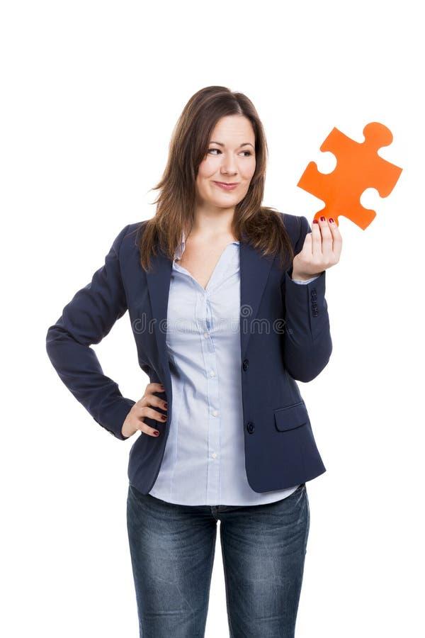 Geschäftsfrau, die ein Puzzlespielstück hält lizenzfreie stockbilder