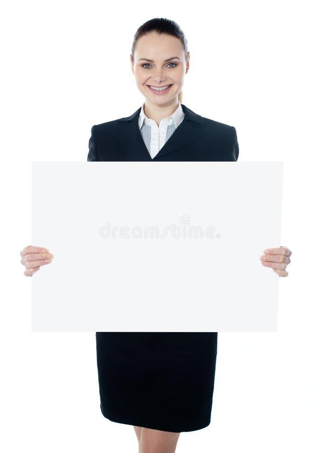 Geschäftsfrau, die ein unbelegtes weißes Plakat anhält lizenzfreies stockfoto