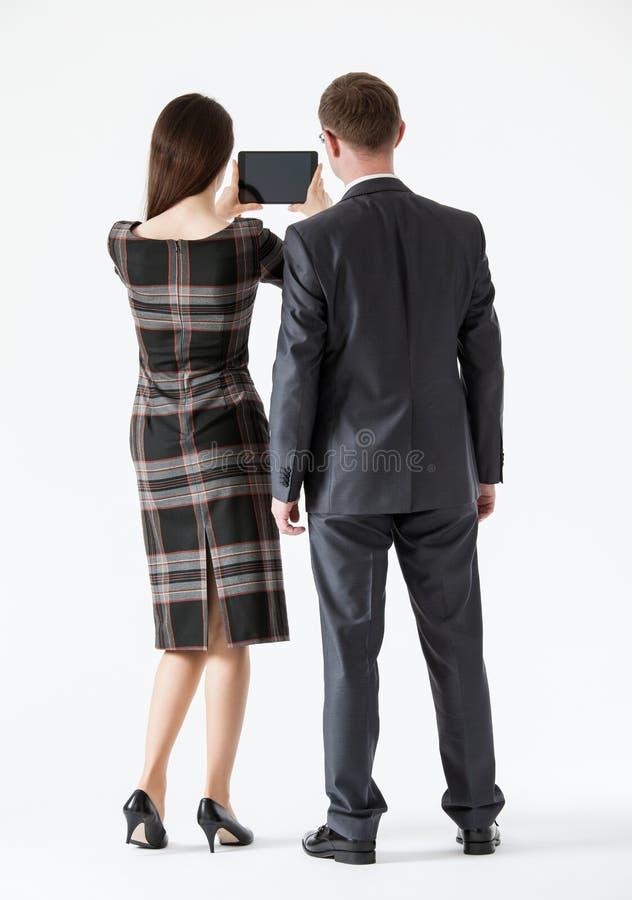 Geschäftsfrau, die eine Auflage hält und ihrem Partner etwas zeigt lizenzfreie stockfotografie