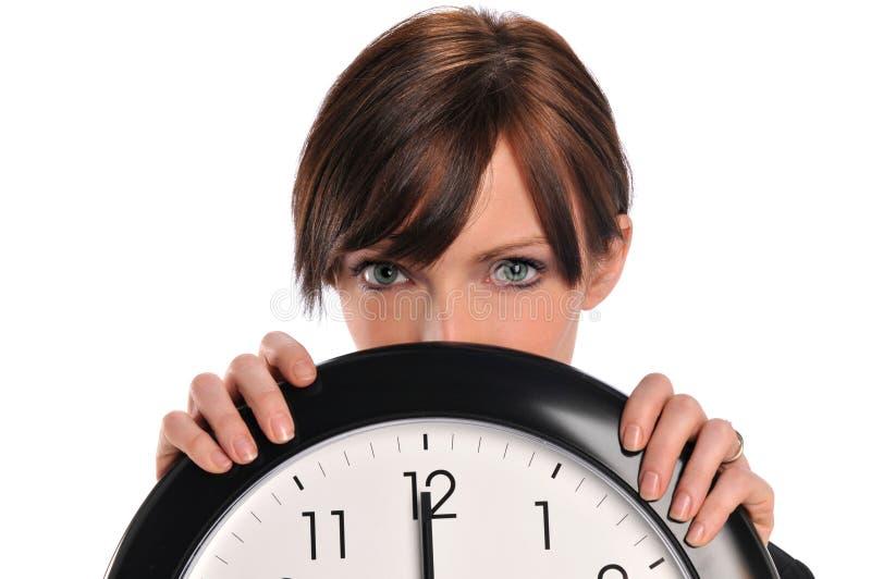 Geschäftsfrau, die eine Borduhr anhält stockbild