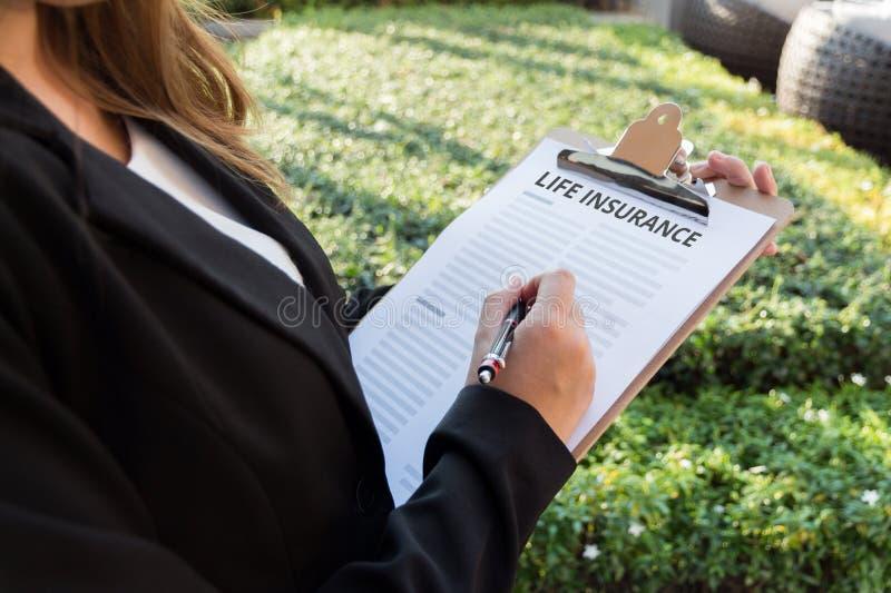 Geschäftsfrau, die eine Lebensversicherungspolice auf der Straße unterzeichnet lizenzfreie stockfotos