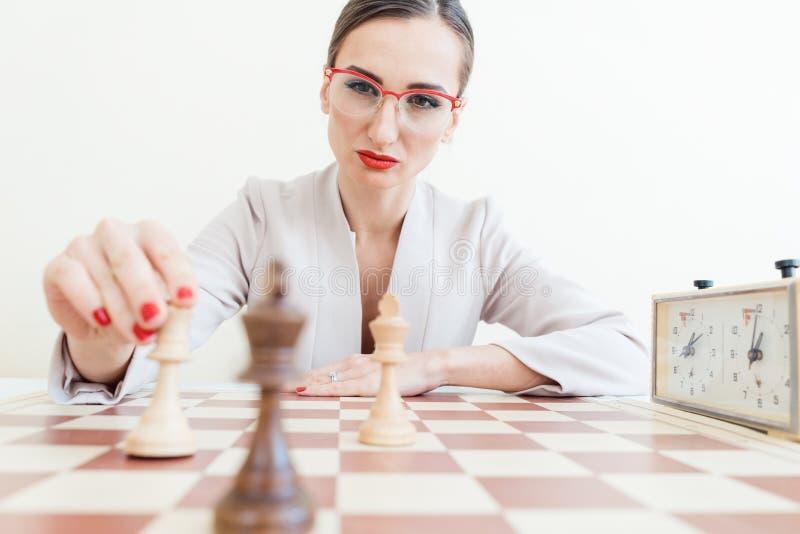 Geschäftsfrau, die eine Maßnahme im Spiel des Schachs trifft lizenzfreie stockfotos