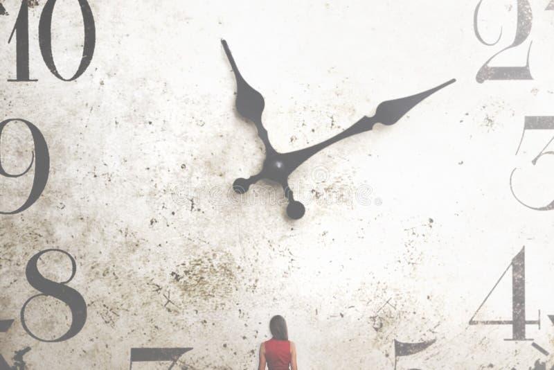Geschäftsfrau, die eine riesige Uhr betrachtet lizenzfreies stockfoto