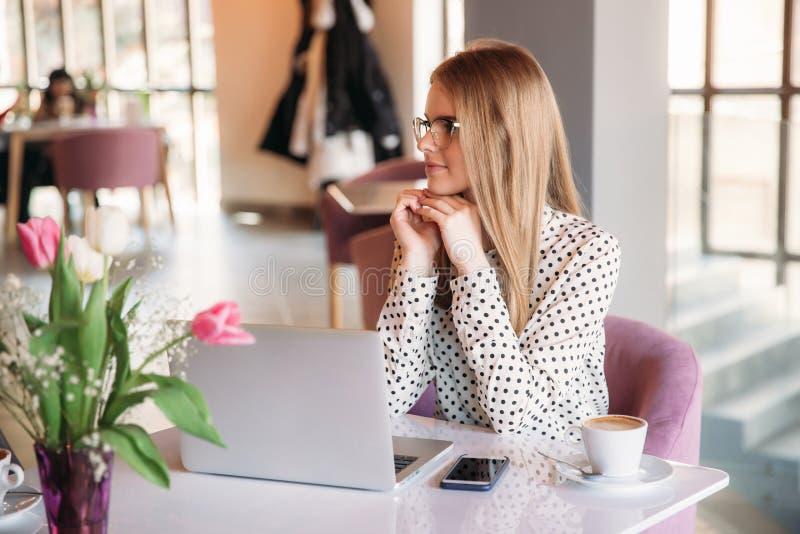 Geschäftsfrau, die in einem Café bearbeitet und zu Mittag isst lizenzfreie stockbilder