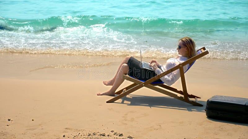 Geschäftsfrau, die an einem Laptop beim Sitzen in einem Ruhesessel durch das Meer auf einem weißen sandigen Strand arbeitet freib stockfoto