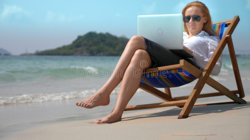 Geschäftsfrau, die an einem Laptop beim Sitzen in einem Ruhesessel durch das Meer auf einem weißen sandigen Strand arbeitet freib stockfotografie