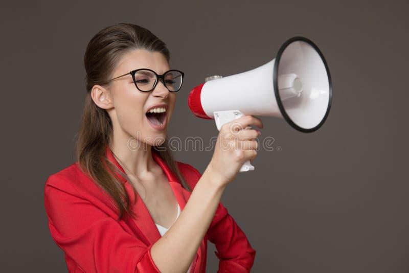 Geschäftsfrau, die an einem Megaphon schreit Junges hübsches Mädchen in den Gläsern und in einer roten Jacke stockbild