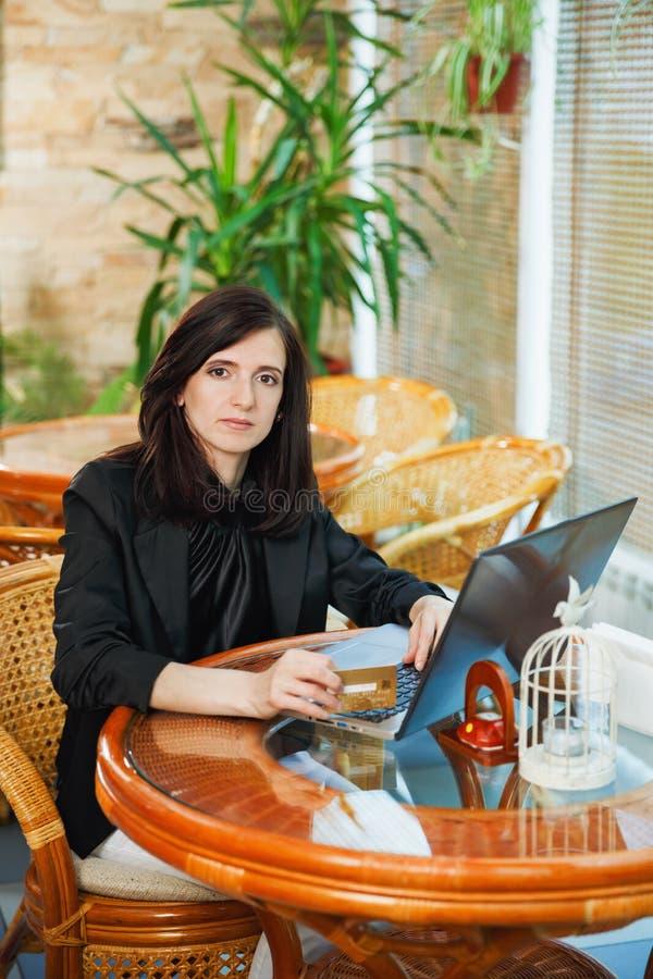 Geschäftsfrau, die an einem Tisch in einem Café mit einem Laptop und einem a sitzt stockbild