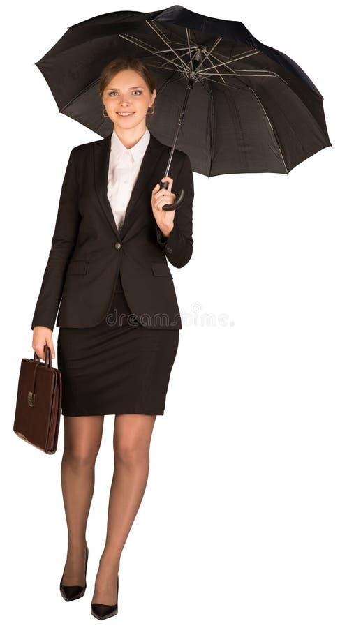 Geschäftsfrau, die einen Aktenkoffer und einen Regenschirm hält lizenzfreie stockfotografie