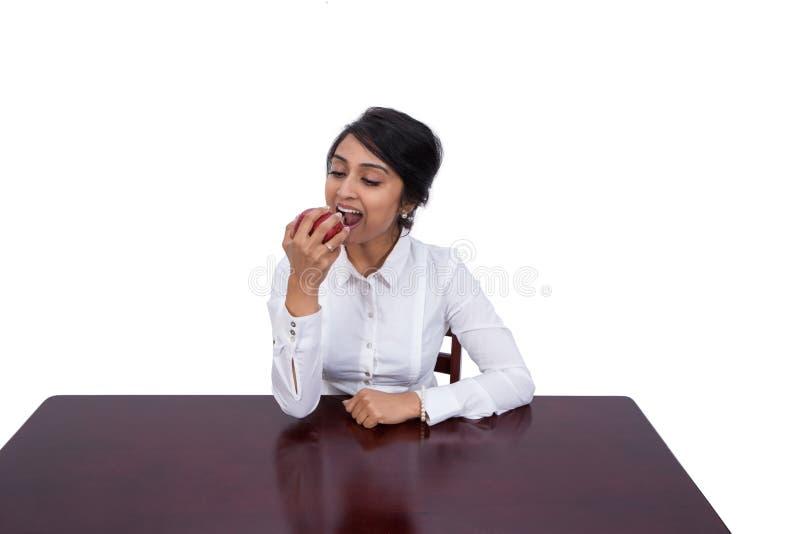 Geschäftsfrau, die einen Apfel isst lizenzfreie stockfotos