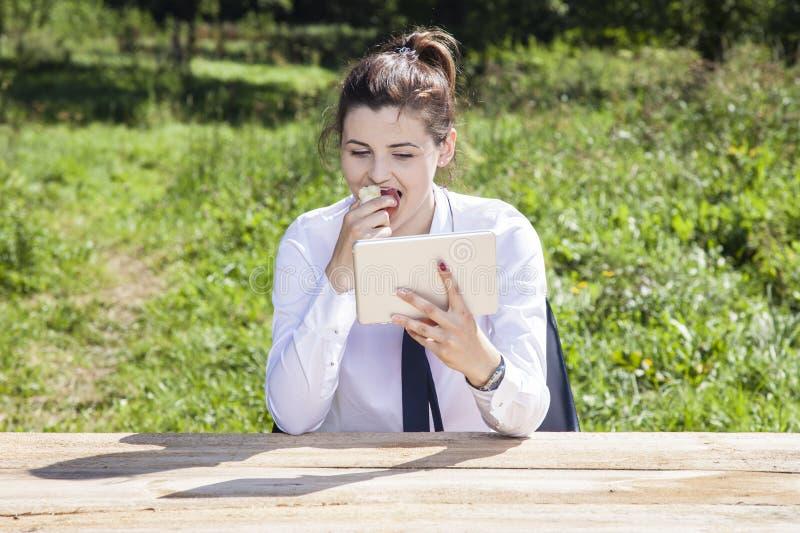 Geschäftsfrau, die einen Apfel isst und Mitteilungen liest lizenzfreies stockbild