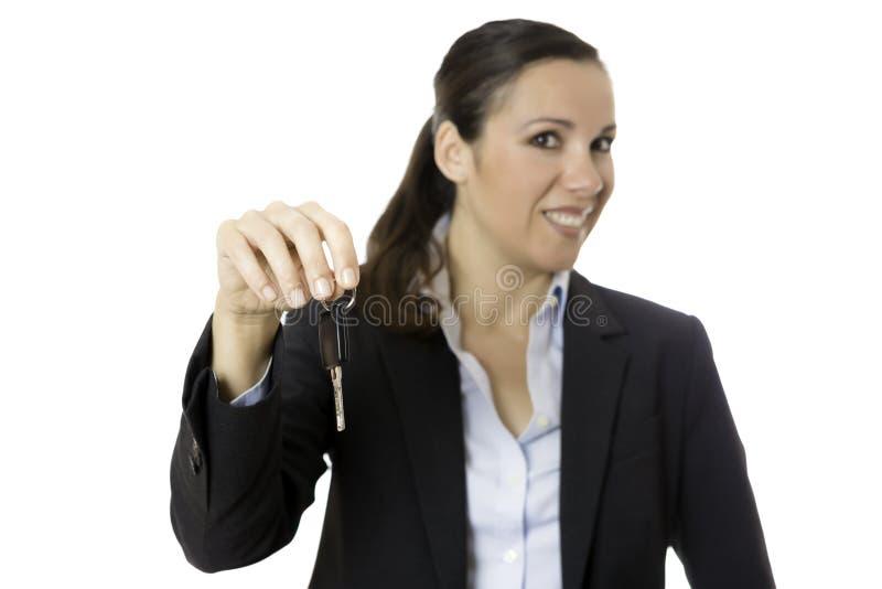 Geschäftsfrau, die einen Autoschlüssel anbietet stockbilder