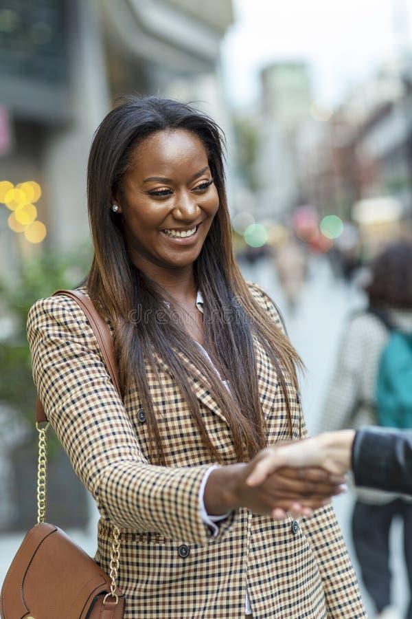 Geschäftsfrau, die einen formalen Händedruck anbietet lizenzfreie stockbilder