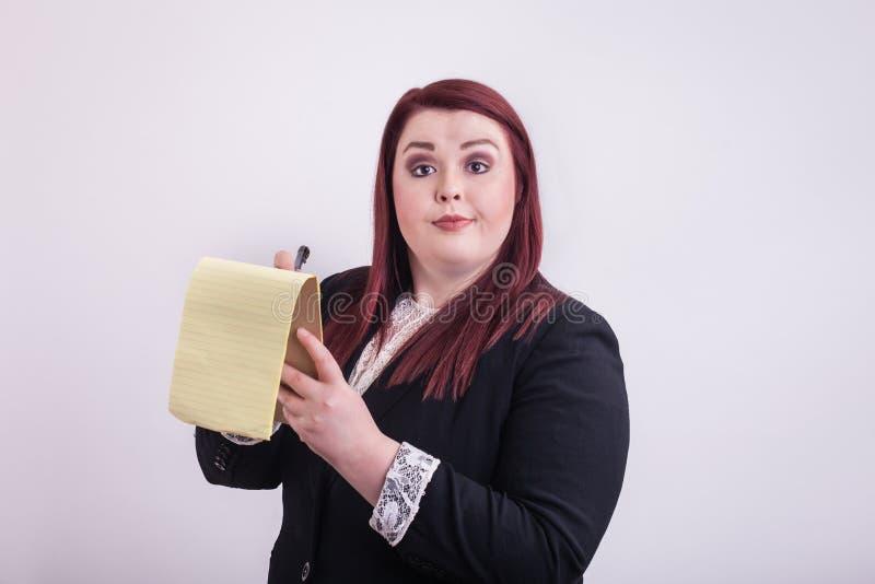 Geschäftsfrau, die einen gelben Notizblock nimmt Kenntnisse hält lizenzfreie stockfotos