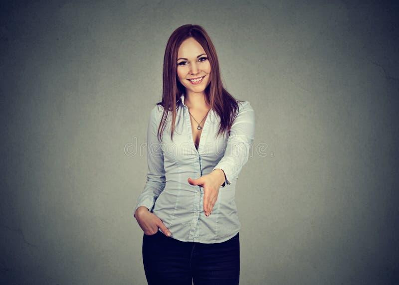 Geschäftsfrau, die einen Händedruck lokalisiert auf grauem Hintergrund gibt stockfotos