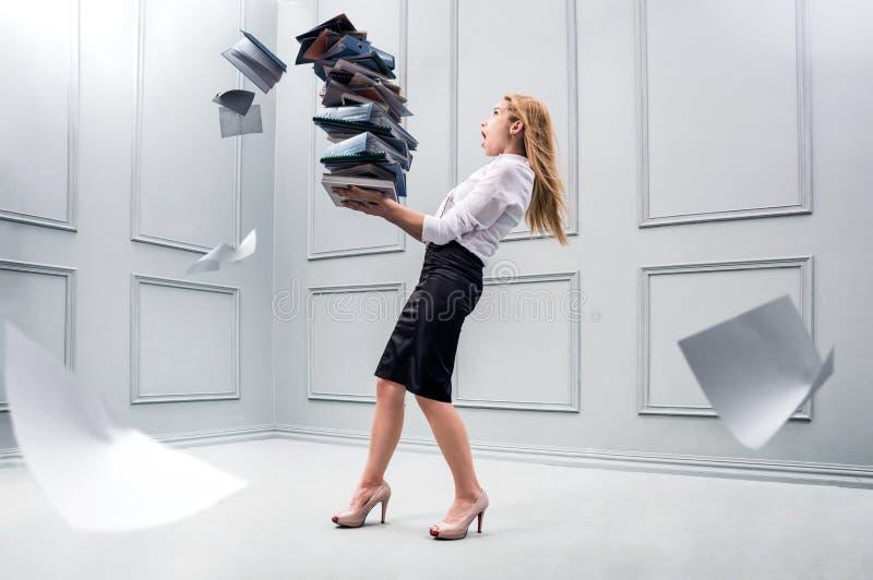 Geschäftsfrau, die einen Stapel von Papieren trägt stockfotografie