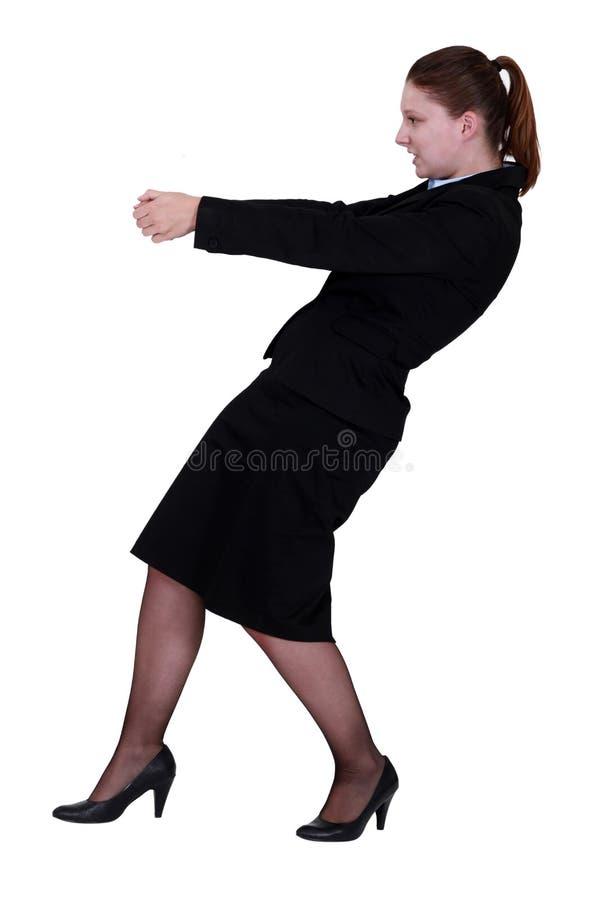 Geschäftsfrau, die einen unsichtbaren Gegenstand zieht stockfotos