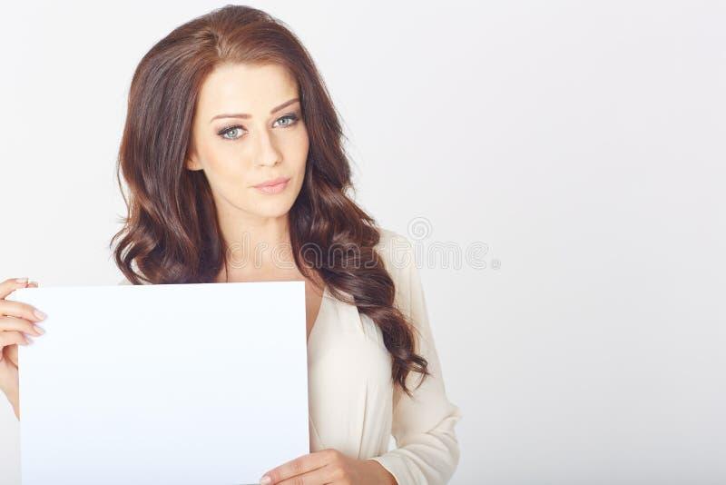 Geschäftsfrau, die einen weißen Vorstand anhält stockfotografie