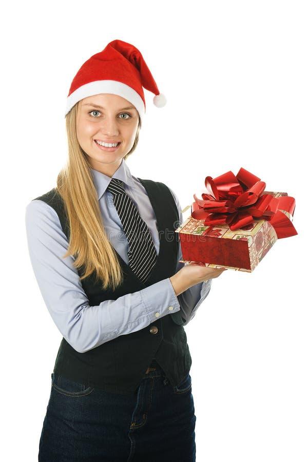 Geschäftsfrau, die einer Sankt den Hut mit einem Geschenk trägt stockbild