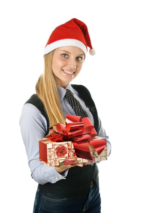Geschäftsfrau, die einer Sankt den Hut mit einem Geschenk trägt stockfoto