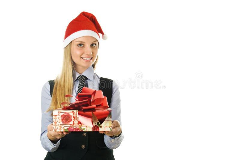 Geschäftsfrau, die einer Sankt den Hut mit einem Geschenk trägt lizenzfreies stockfoto