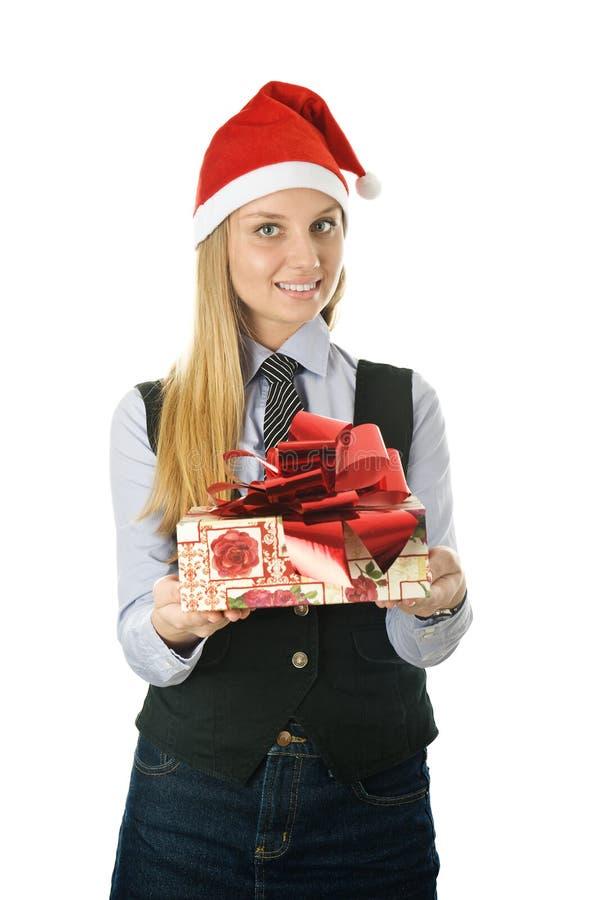 Geschäftsfrau, die einer Sankt den Hut mit einem Geschenk trägt lizenzfreies stockbild