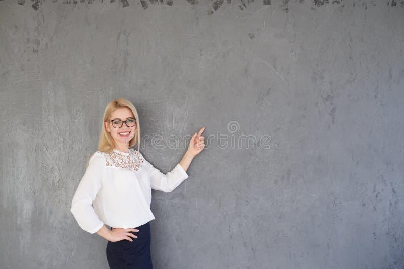 Geschäftsfrau, die Finger auf grauem Hintergrund zeigt stockbild